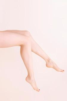 Kobiece gołe nogi unoszą się, na beżowej ścianie. salon piękności, depilacja, opieka, medycyna, żylaki, chirurgia plastyczna, spa i koncepcja leczenia.
