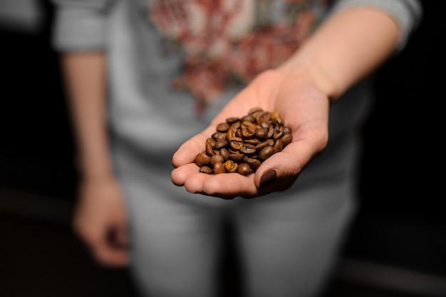 Kobiece handd gospodarstwa garść świeżych ziaren kawy