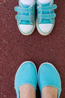 Kobiece i dziecięce stopy w sportowych turkusowych butach trampki leżą na ziemi w zbliżeniu w parku
