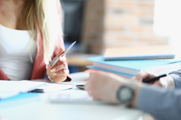 Kobiece i męskie dłonie z długopisami z zeszytami przy stole roboczym