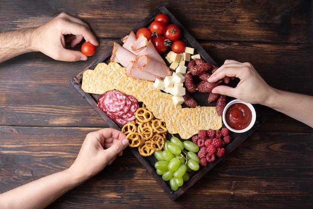 Kobiece i męskie ręce biorąc przekąski z deski wędlin z kiełbasą, owocami, krakersami i serem na ciemnym tle drewnianych, zbliżenie.