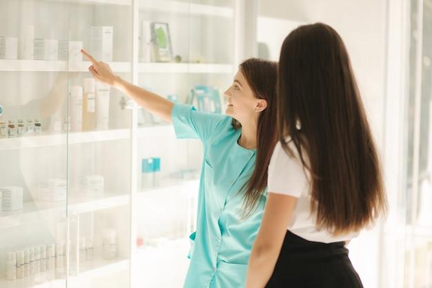 Kobiece kosmetyczki pokazują klientowi produkt kosmetyczny. lekarz zaleca inne serum i twarz