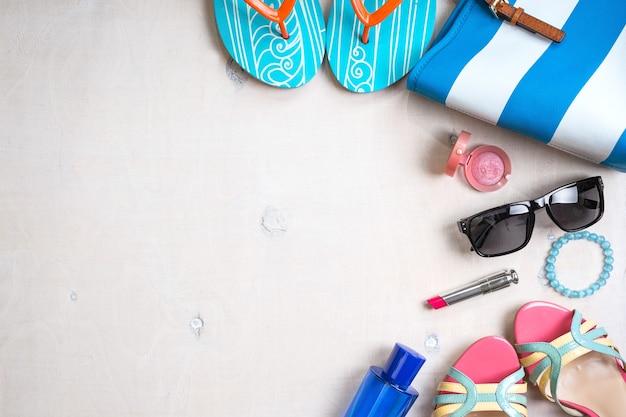 Kobiece lato tło. zestaw letnich akcesoriów damskich: okulary przeciwsłoneczne, buty, kapcie, torebka w niebieskie paski, różowa szminka, rumieniec, perfumy na białym tle drewna.