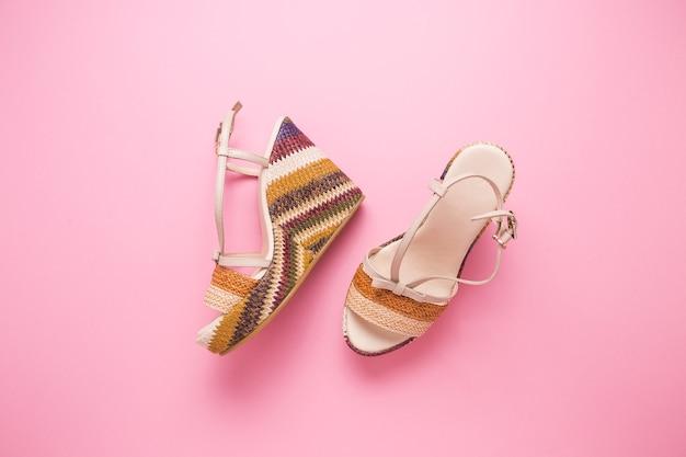 Kobiece letnie sandały na różowym tle z bliska.