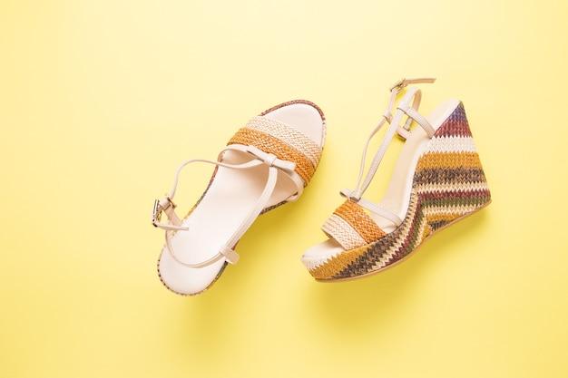 Kobiece letnie sandały na żółtym tle z bliska.
