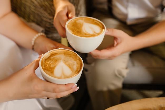 Kobiece, męskie dłonie trzymają kubki z kawowym zbliżeniem. koncepcja czasu na kawę.