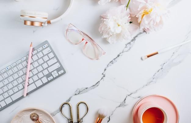 Kobiece miejsce do pracy w domu z filiżanką herbaty i kwiatami piwonii na białym marmurowym tle widok z góry ...