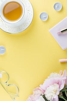 Kobiece miejsce do pracy z kalendarzem, kwiatami piwonii, kosmetykami, zieloną herbatą