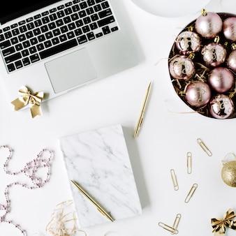 Kobiece miejsce do pracy z laptopem, marmurowy pamiętnik, złoty długopis, świąteczne dekoracje, bombki, blichtr, kokardka na białym tle.