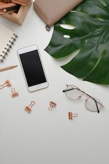 Kobiece miejsce pracy z inteligentnym telefonem, okularami, notatnikiem, portfelem i papeterią na białym tle.