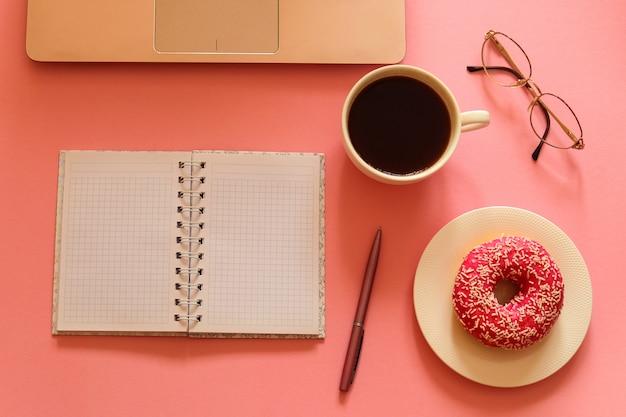 Kobiece miejsce pracy z laptopem, pączkiem, kawą, notatnikiem, okularami i długopisem na różowym stole