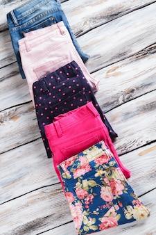 Kobiece niebieskie dżinsy i spodnie. spodnie w kwiaty z niebieskimi dżinsami. wysokiej jakości odzież z nowej kolekcji. ubierz się na każdy dzień.