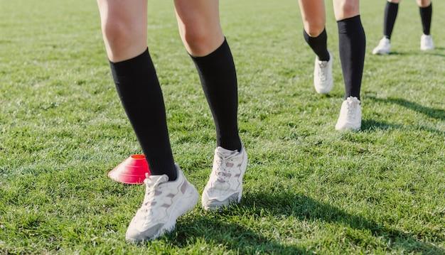 Kobiece nogi biegnące przez szyszki