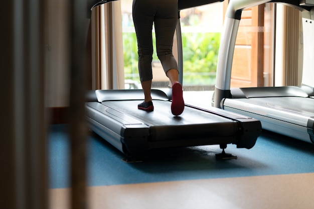 Kobiece nogi chodzenia i biegania na bieżni w siłowni. trening cardio