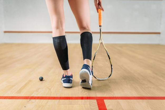 Kobiece nogi gracza w squasha, rakieta i piłka, kryty klub treningowy