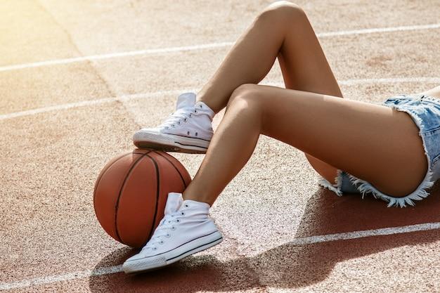 Kobiece nogi i piłka do koszykówki
