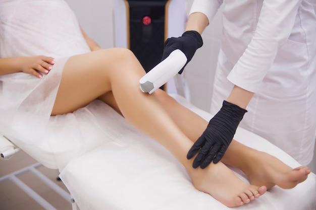 Kobiece nogi, kobieta w profesjonalnej klinice urody podczas depilacji laserowej