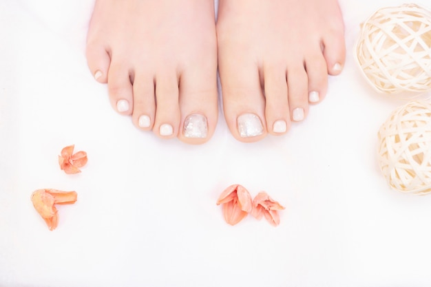 Kobiece nogi na białym tle. paznokcie nabierają świeżego i zgrabnego wyglądu podczas zabiegu pedicure