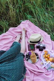 Kobiece nogi na różowym kocu na trawie, na zewnątrz świeże owoce, jagody i ciasta