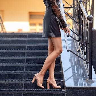 Kobiece nogi na schodach w profilu