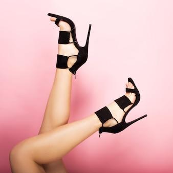 Kobiece nogi na wysokich czarnych obcasach na różowym tle