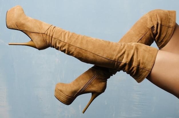 Kobiece nogi w beżowych zamszowych butach na obcasie