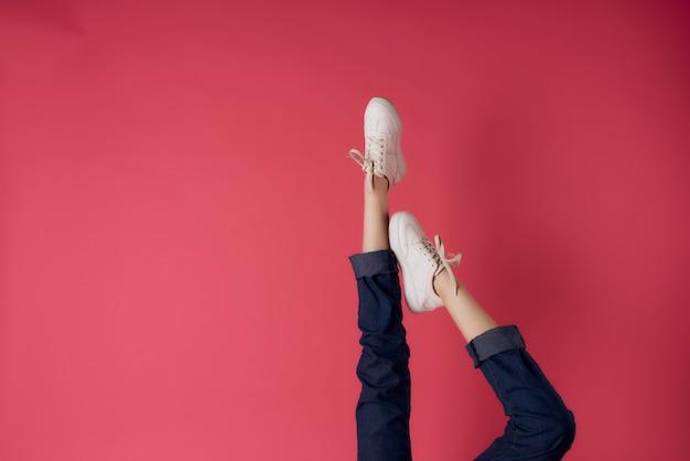 Kobiece nogi w białych trampkach do góry nogami widok różowego tła mody