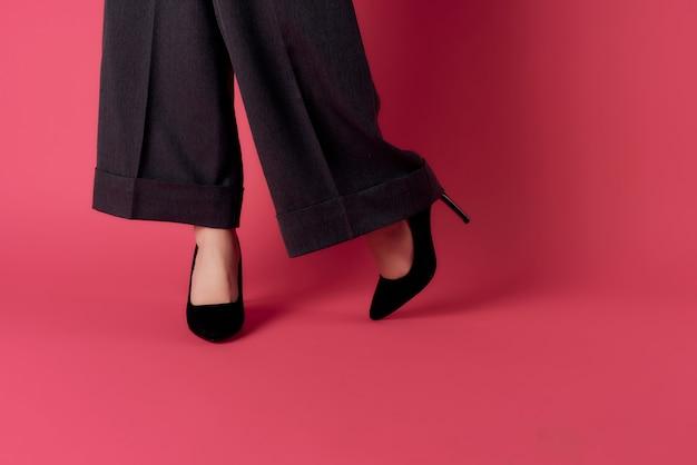 Kobiece nogi w czarnych butach pozowanie różowym tle w nowoczesnym stylu. zdjęcie wysokiej jakości