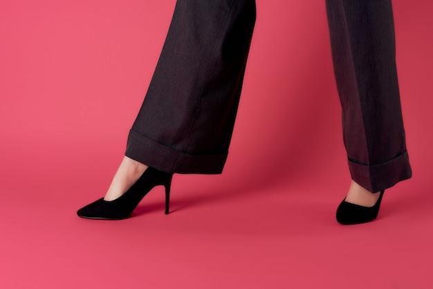 Kobiece nogi w czarnych butach pozują na różowym tle w nowoczesnym stylu