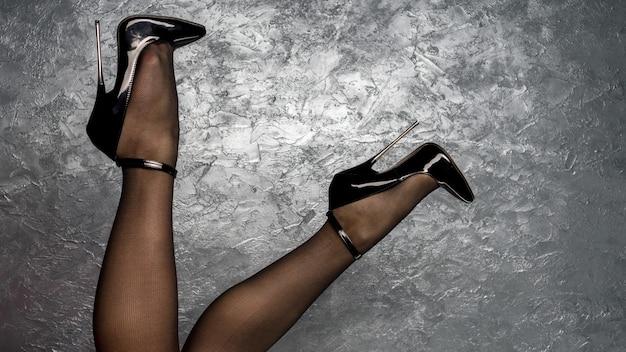 Kobiece nogi w czarnych fetyszowych błyszczących szpilkach ze skóry lakierowanej z paskiem na kostkę w pobliżu ściany sztukaterii weneckiej