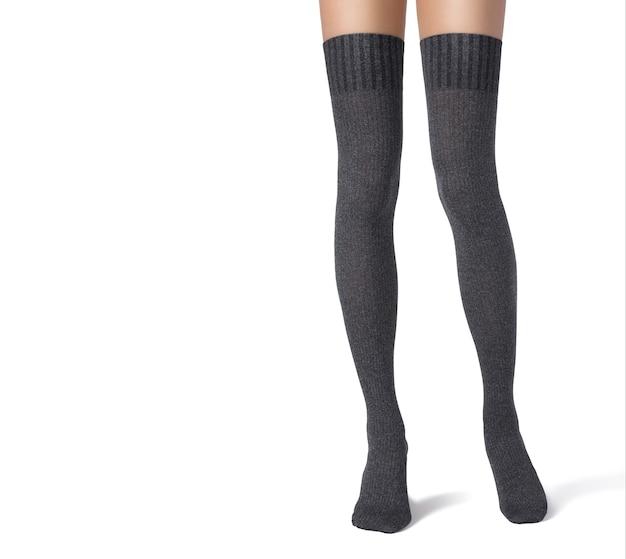 Kobiece nogi w czarnych rajstopach do połowy uda na białym tle