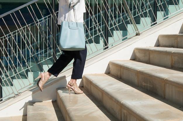 Kobiece nogi w czarnych spodniach z niebieską torbą stojącą na schodach