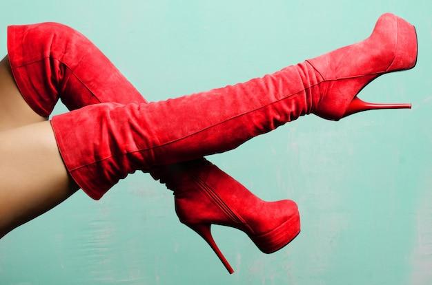 Kobiece nogi w czerwonych zamszowych butach na obcasie