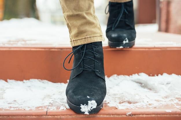 Kobiece nogi w eleganckich butach zimowych na ośnieżonych schodach, zbliżenie
