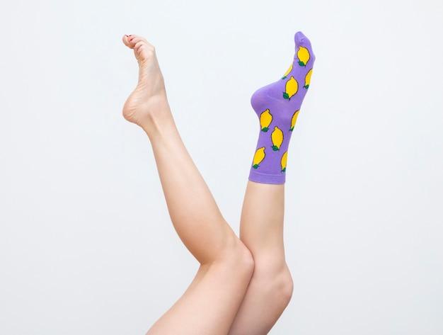 Kobiece nogi w kolorowych skarpetkach z cytrynami na białym tle
