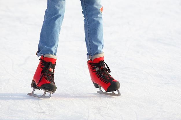 Kobiece nogi w łyżwy na lodowisku