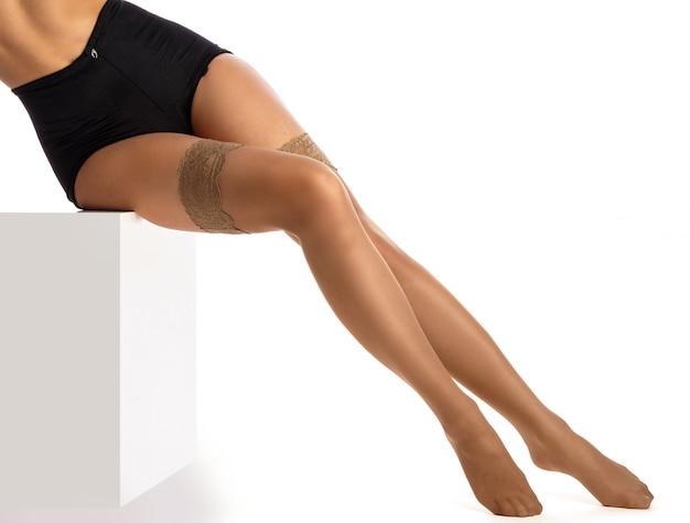 Kobiece nogi w nagich pończochach