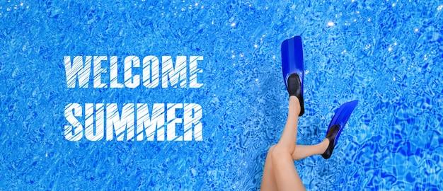 Kobiece nogi w płetwach na tle basenu, panoramiczny obraz z napisem witamy lato