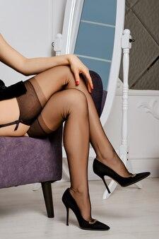 Kobiece nogi w pończochach i pas do pończoch siedząc w fotelu
