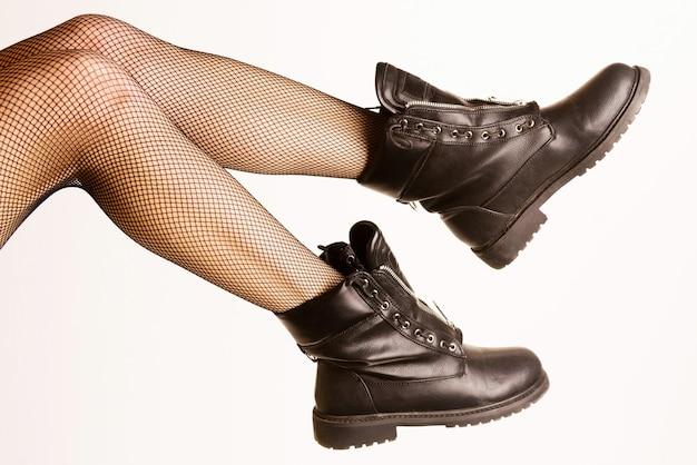 Kobiece nogi w seksownych rajstopach i czarnych wojskowych butach