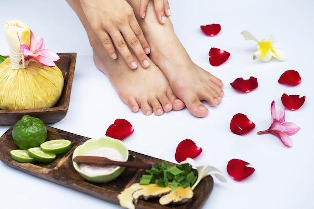 Kobiece nogi w wodzie dekoracji kwiatów. kobieta poddawana zabiegowi pedicure w spa lub salonie kosmetycznym z masażem pedikiurzysty