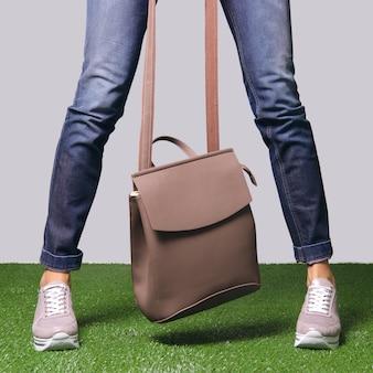 Kobiece nogi w wygodnych miejskich tenisówkach i skórzanej torbie w rękach