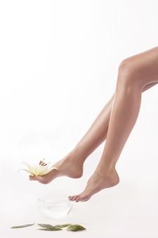 Kobiece nogi z białą lilią na białym tle