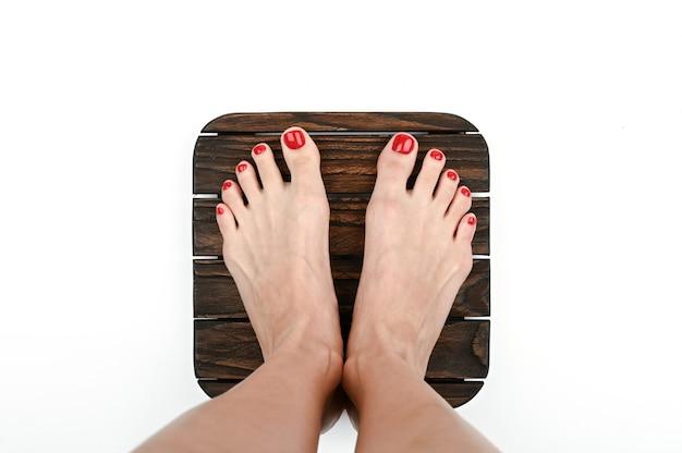 Kobiece nogi z pomalowanymi paznokciami na drewnianej powierzchni