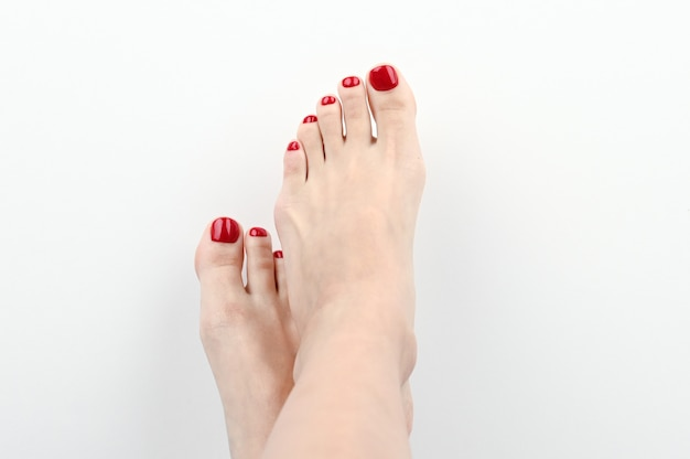 Kobiece nogi z pomalowanymi paznokciami w kolorze czerwonym. na odosobnionej przestrzeni