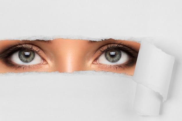 Kobiece oczy w papierowej dziurze