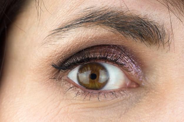Kobiece oko z bujnymi rzęsami i makijażem powiek, zbliżenie.