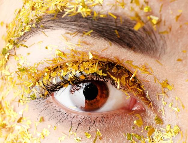 Kobiece oko z fantazyjnym makijażem brokatu, widok makro