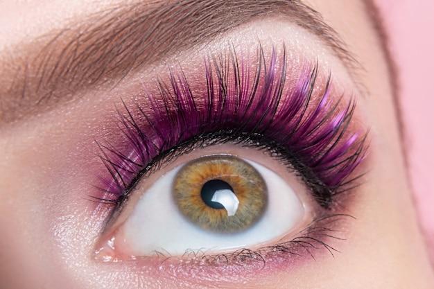 Kobiece oko z fioletowymi cieniami i sztucznymi rzęsami