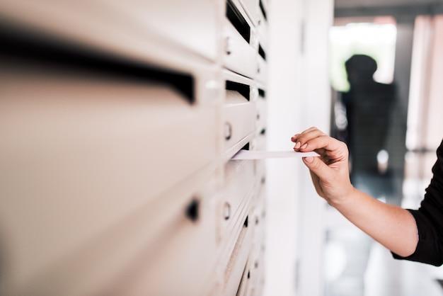 Kobiece osoby wprowadzenie list w metalowej skrzynce pocztowej, zbliżenie.